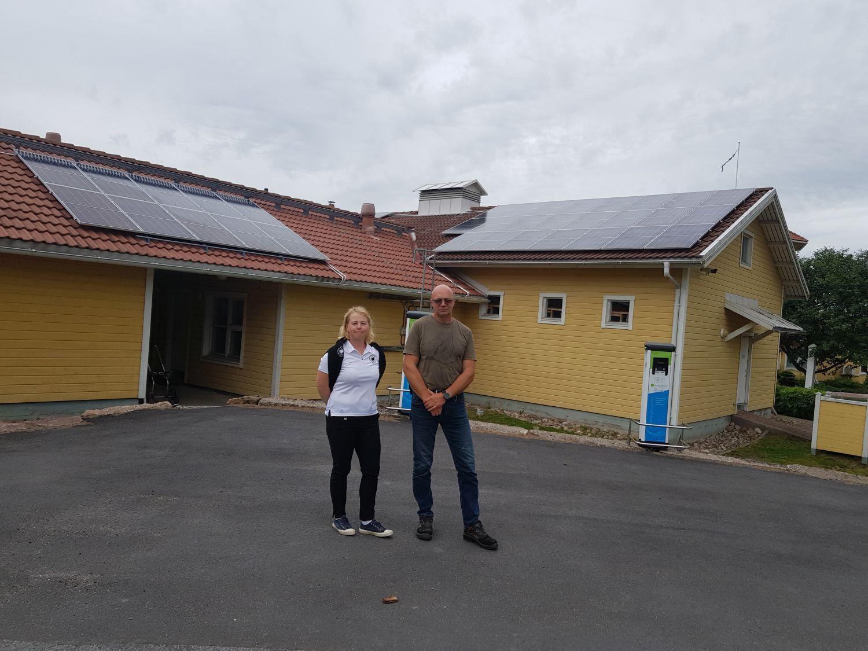 två personer framför hus