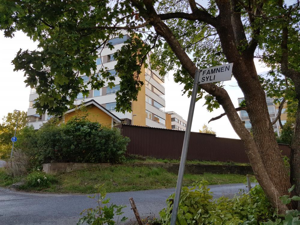 gult höghus i bakgrunden, skylt med gatunamn samt buskar