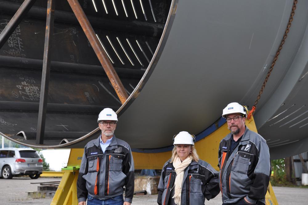 tre personer i vita bygghjälmar framför enorm metallkonstruktion