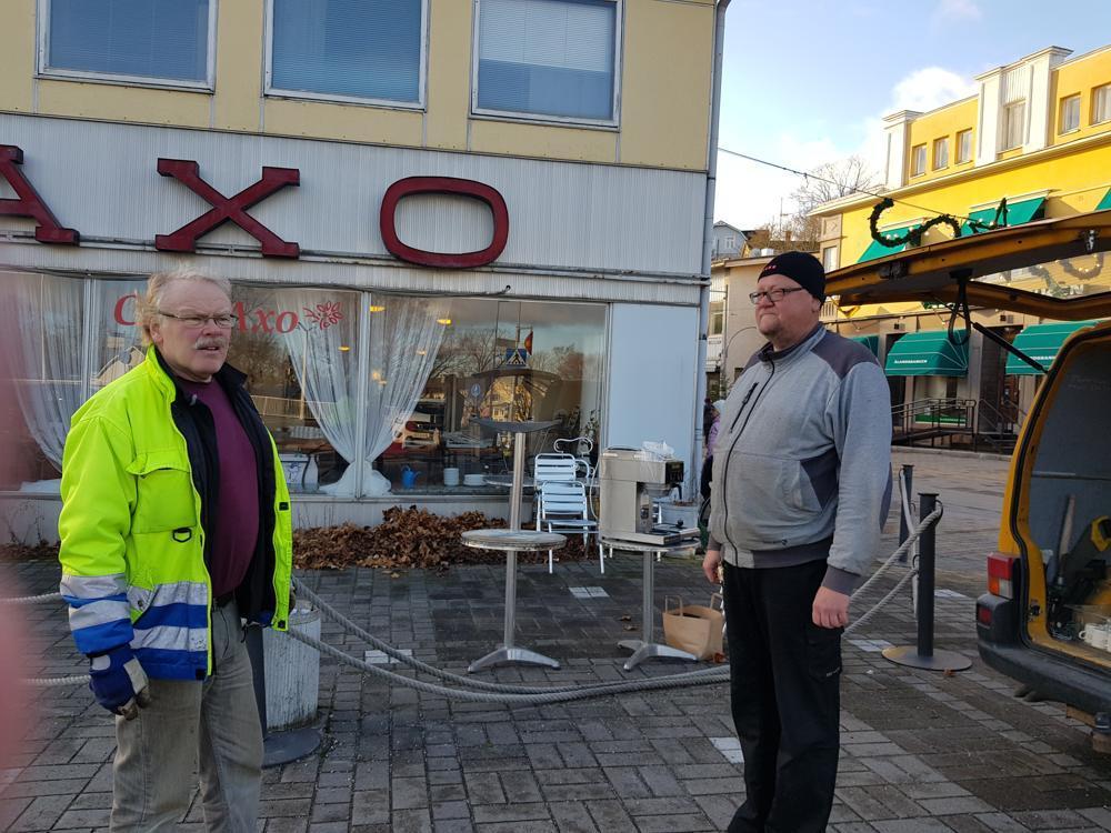 Två män utanför stängt café